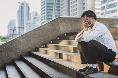 overly: Young depressed businessman sitting on the stairs Stock Photo