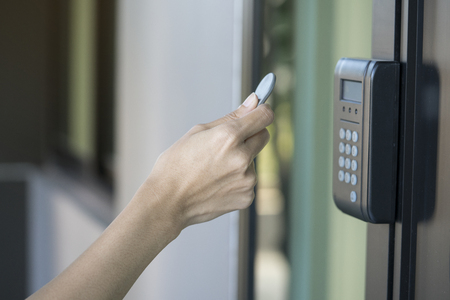young woman using RFID tag key to open the door