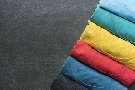 close up of rolled colorful clothes on black background Stockfoto