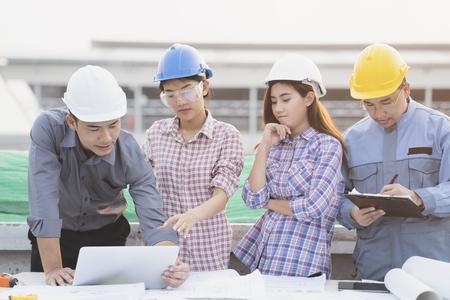 Los ingenieros asiáticos fueron consultados juntos y planean en el sitio de construcción Foto de archivo - 78995092