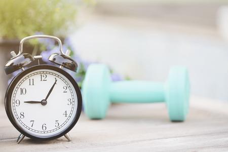 時計とダンベル、スポーツ コンセプトを行使するための時間