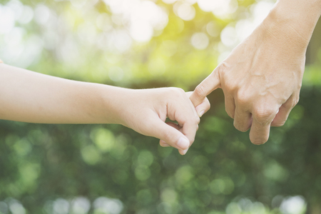 A mother and her child hooking their fingers to make a promise Stock Photo
