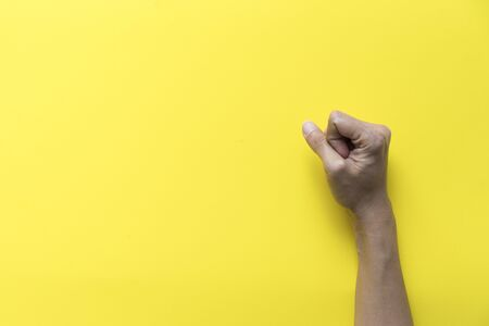 Female fists clenched on yellow table background table in stress emotion