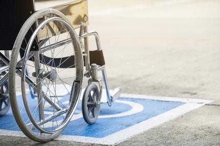 Pavement handicap symbol and wheelchair Stock Photo