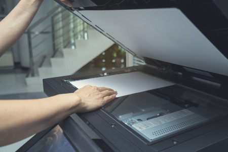 xerox: woman hand putting a sheet of paper into a copying device