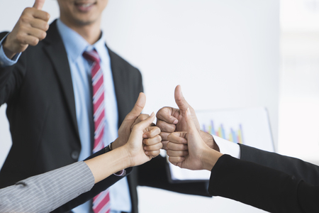 collaborator: Close-up of business team holding their thumbs up, business success concept
