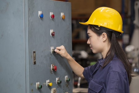 young asian woman engineer set up and testing old machine in the laboratory factory, engineering and industrial concept