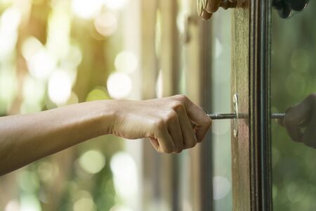 dirty room: female hand putting house key into front door lock of house Stock Photo