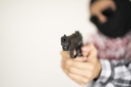 criminal: Hand of terrorist holding a gun