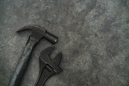 Close up hammer and monkey wrench on grunge cement background Stock Photo