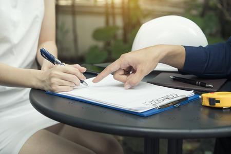 Een onderneemster onderhandelt een bedrijfsovereenkomst of contracting en ondertekening van een contract, concept van zakelijke onderhandelingen
