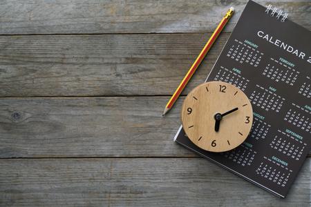 Nahaufnahme von Uhr, Kalender und Bleistift auf dem Tisch, Planung für Geschäftstreffen oder Reiseplanung Konzept