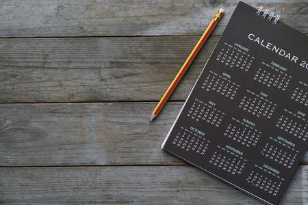 Nahaufnahme von Kalender und Bleistift auf dem Tisch, Planung für Geschäftstreffen oder Reiseplanung Konzept