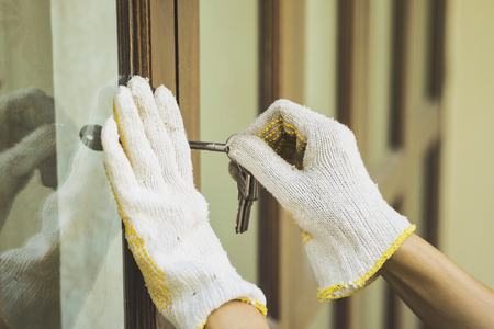 Burglar with passkey tools breaking and entering into a house Stock Photo