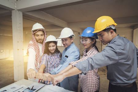 Asian engineers were consulted together and trust in team giving fist bump to plan in construction site