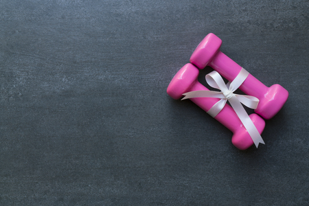 two pink dumbbell with white gift bow on a black table background, sport and healthy concept
