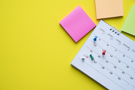 close up of calendar on yellow background, planning for business meeting or travel planning concept Foto de archivo