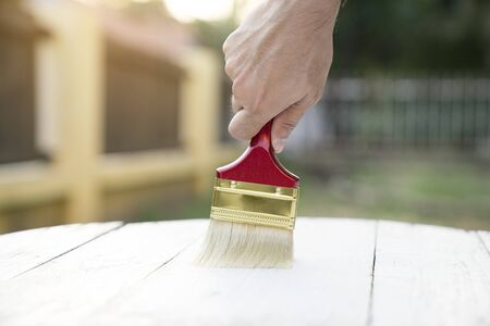 Applying protective varnish on a wooden texture, diy and repair house equipment concept