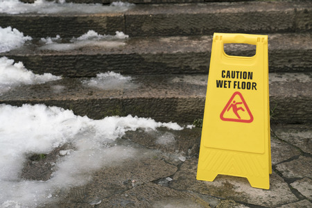 Warning sign for wet floor with snow, outdoor