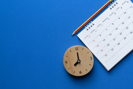 Nahaufnahme von Kalender, Uhr und Bleistift auf dem blauen Hintergrund, Planung für Geschäftstreffen oder Reiseplanungskonzept Standard-Bild