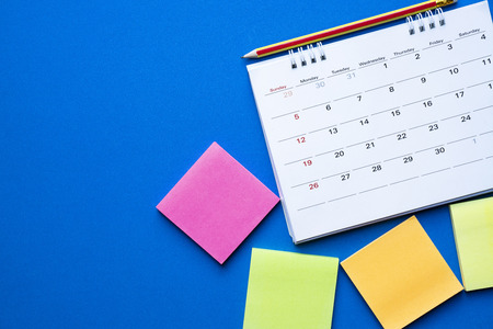 close up of calendar on the table with blue background, planning for business meeting or travel planning concept