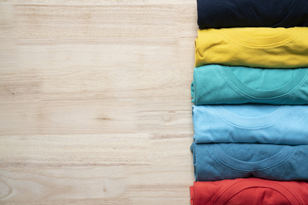 close up of rolled colorful clothes on the wooden table background