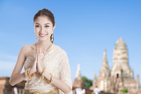 Thai woman in Thai dress costume traditional in a welcome pose, hello Sawadee with temple background