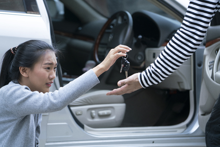 Woman struggled with a car robber or mugger, cannot resist and have to give a robber her key reluctantly