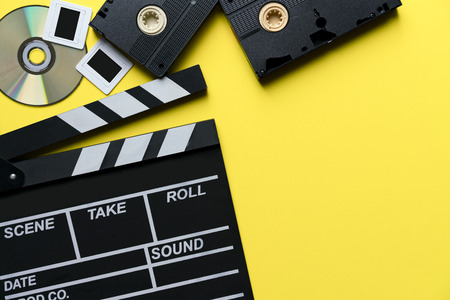 movie clapper, cd, video cassette tapes on yellow table ; film, cinema and video photography concept