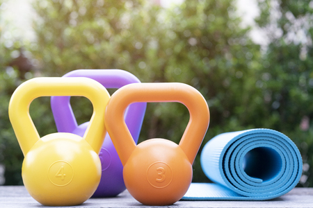 Kettlebells and blue yoga mat on wood table, sport and healthy concept