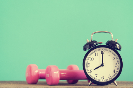 Time for exercising clock and dumbbell with colorful green background, retro style