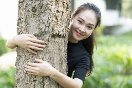 Close-up of a smiling asian young woman hugging tree at the park