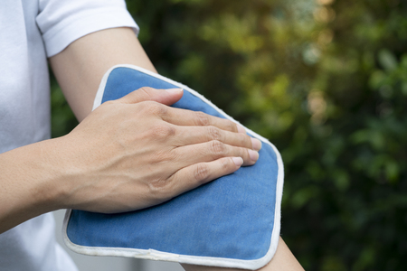 woman putting an ice pack on her arm pain, healthy concept