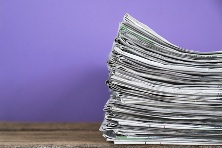 close up newspapers folded and stacked background on the table with purple background