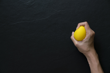 woman holding a stress ball in her hand on black background Banco de Imagens