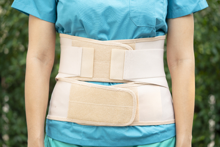 young Asian woman wearing back support to protect her back Banco de Imagens