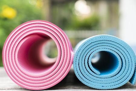 Nahaufnahme von Yogamatten auf dem Tisch, Sport und gesundes Konzept Standard-Bild