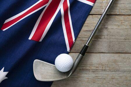 Golf ball with flag of Australia on wood table