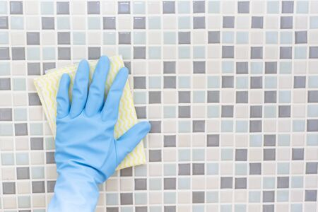 Cleaning tile wall by woman hand with glove, ready to clean house on bathroom background Stockfoto
