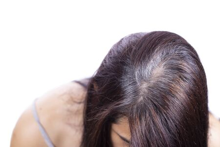 La giovane donna mostra le sue radici di capelli grigi, fondo isolato e bianco Archivio Fotografico