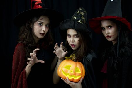 Young Asian people, a group of three women, in scary costumes. Group of friends wearing Halloween clothes preparing to join a party. Stock Photo