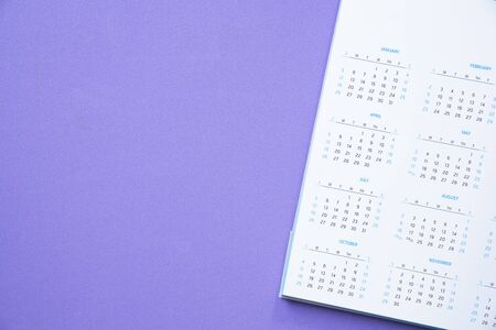 close up of calendar on the purple table background, planning for business meeting or travel planning concept