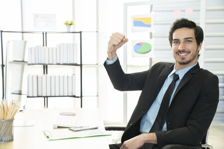 Portrait of businessman pushing his hand up to cheer up, business success concept
