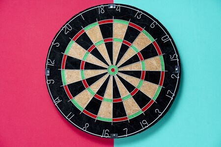 target dart board on the red and table background, center point, head to target marketing and business success concept