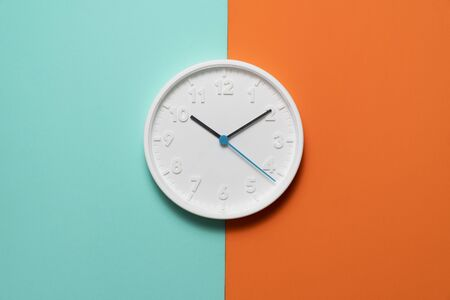 Retro white clock on green and orange color table background, vintage style