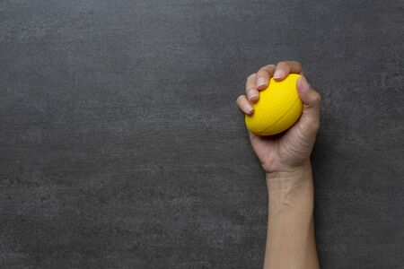woman hand holding stress ball on black table background, stress concept