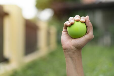 Hands of a woman squeezing a green stress ball, close up