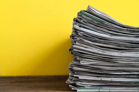 close up newspapers folded and stacked on yellow background on the table Stock Photo