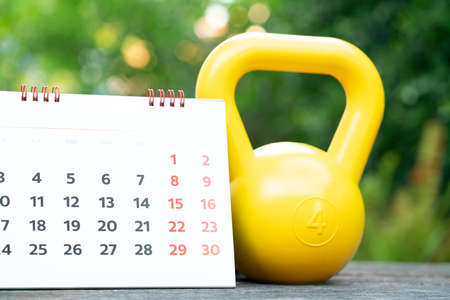 Time for exercising calendar and kettlebell sport equipment on the table background Stock fotó
