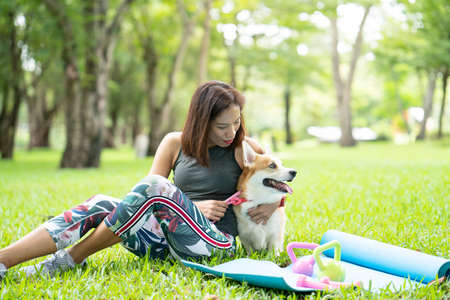 A healthy woman playing with a corgi puppy while excersing on yoga mat surrounding with gym tools such as kettlebell and dumbbell, outdoor training with dog